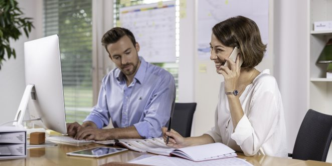 Male and female project manager collaborating in front of computer screen at office, Fast Forward Procurement